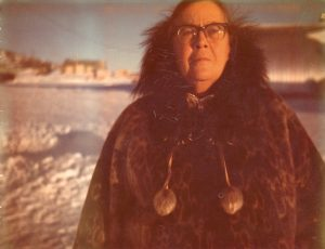 Colour photo of woman in glasses and fur coat with snowy town in background.