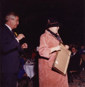 Colour photograph with a woman wearing a hat and suede jacket, holding a frame; man in a suit stands behind her and a crowd of people seated at tables look on.