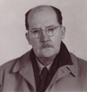 Black and white photo of an older man with glasses and a moustache wearing a coat and tie.