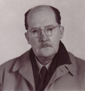 Photo noir et blanc d'un homme âgé avec des lunettes et une moustache, portant manteau et cravate.
