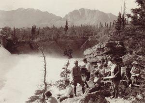 Photo sépia d'un groupe d'artistes faisant des croquis sur la rive surplombant une chute d'eau dans un paysage d'arbres et de montagnes.