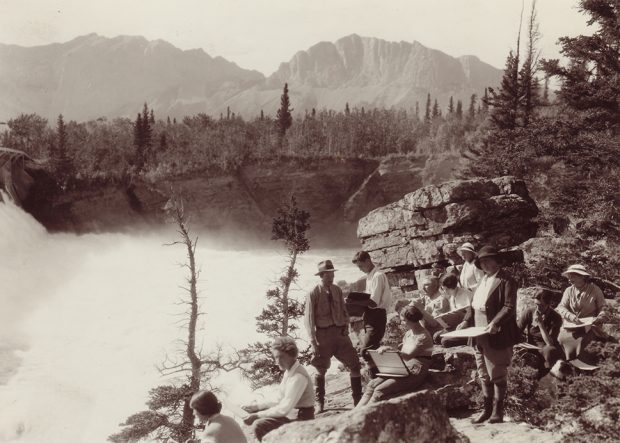 Sepia photo of group of artists sketching on bank overlooking a waterfall in treed and mountain landscape.