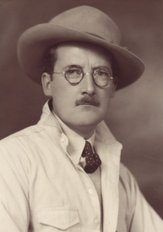 Sepia studio portrait of man with moustache wearing glasses, felt hat, tie and light coloured jacket.