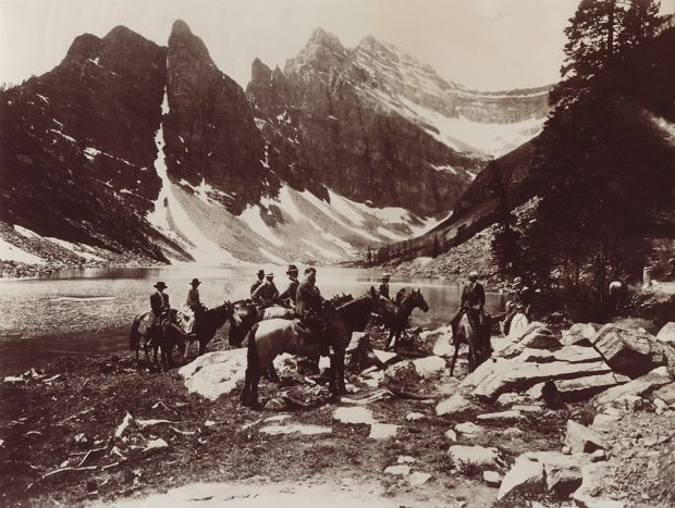 Sepia photo of a group of people riding horses next to a lake in a mountain landscape.