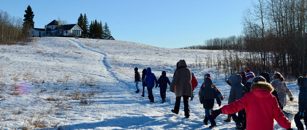 Colour photo of a line of children walking single file up a hill in a winter landscape towards a half timbered house.