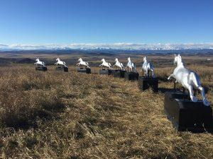 Photo couleur d'un paysage avec huit chevaux mécaniques à pièces alignés devant le panorama de la montagne.