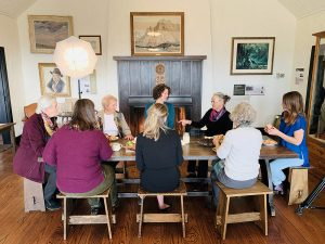 Colour photograph of group of women eating around table; artwork on walls in background.