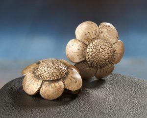 Silver earrings in the shape of small six petalled flowers.