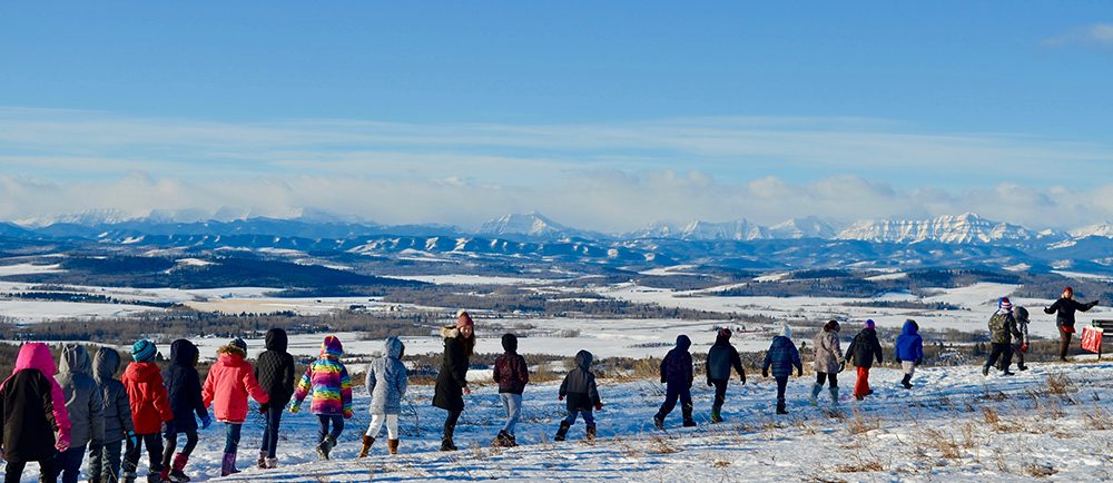 Colour photo of a line of children walking single file in front of a winter panorama of mountains in the distance.