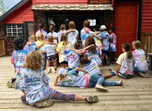 Photo couleur d'un groupe d'enfants sur une terrasse, portant des t-shirts teints avec effet tie-dye, devant un bâtiment rouge.