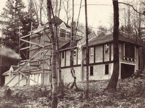 Photo noir et blanc d'une maison à colombages avec un échafaudage sur le côté et entourée d'arbres.
