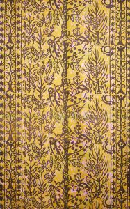 Block printed textile yardage with a brown design of birds, leaves and flowers on a ground of pale pink and chartreuse.