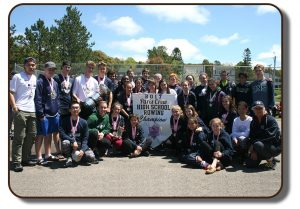 An image of a group of students from Rothesay Netherwood School who were awarded The Paris Crew trophy in the Summer of 2017. The students are holding up a banner which reads 2017 Paris Crew High School Rowing Champions. Each of the team members present in the photograph are wearing a medal around their neck with a pink ribbon lanyard.