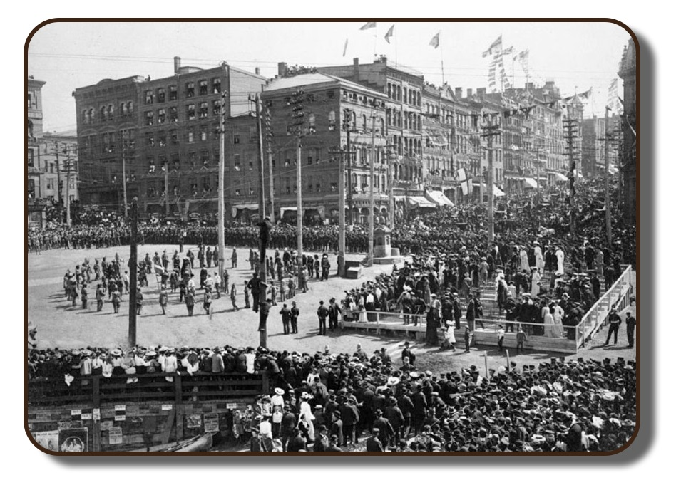 A black and white image of what a city-wide celebration in downtown Saint John, New Brunswick would have looked like in 1867, upon the arrival of The Paris Crew when they returned from Paris. The intersection of King Street and Water Street are lined with thousands of people. In the opened central square area, celebration activities are being performed for the spectators. A make-shift, multi-level stadium seating area was also erected directly in front of the square. Decorations adorn the store fronts and flags line the telephone poles and lamp posts.