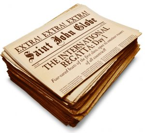 """An image of a period-looking copy of the Saint John Globe newspaper from July 9, 1867. The top copy in the stack of newspapers is showing the front page with the headline """"Extra, Extra, Extra"""" The International Regatta: Day 1. There is also a caption declaring that Four-oared boats of the first class, open to amateur rowers of all countries!"""