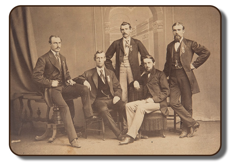 A sepia toned studio photograph of The Paris Crew. All four members and their manager Sherriff J. A. Harding are present in the photograph. The men are all positioned together sitting upon different types of antique furniture. All are wearing formal suit and tie attire, as this photograph was taken as part of the celebrations that took place upon their return from Paris in 1867.