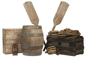 Decorative image of a collage of materials that would have been seen at a dock or pier at the time of The Paris Crew in 1967. The collage includes a wooden barrel with four metal support rings, a wooden trunk, a red kerosene lantern, a bundle of fisherman's rope, two pulleys that would have been used to crank either the sails or mast on a ship, a light birch wood create and two wooden oars.