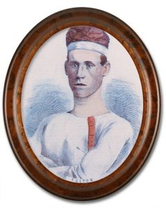 Image of a colourized sketched portrait of Robert Fulton, a team member of the Paris Crew. There is a high gloss oval wooden frame around the portrait. Fulton is wearing a white long-sleeve shirt, with red buttons and is also wearing their signature rowing cap.