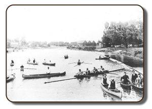 Image d'une berge dans la région de Renforth, à Rothesay, Nouveau-Brunswick, avant la participation de l'équipage de Paris à la Régate internationale d'aviron, en juillet 1867. Cette photographie est en noir et blanc; elle a pâli au fil des années et en raison de l'équipement de photographie personnelle disponible à cette époque. Il y a de nombreuses embarcations sur le cours d'eau, y compris l'aviron à quatre rameurs de l'équipage de Paris, des rameurs seuls dans leur embarcation respective et des canoës comptant une ou deux personnes. Le long de la berge, il y a une zone boisée et on voit ce qui semble être trois granges ou hangars à bateaux.