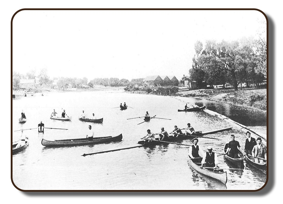 Image of a riverbank in the Renforth area of Rothesay, New Brunswick prior to the Paris Crew's participation in the International Rowing Regatta in July 1867. This photograph is in black and white, and quite faded due to its age and personal photography equipment available at that time. There are a number of different boats on the water including the Paris Crew in their four-person rowing scull, single rowers, and others in one-person and two-person canoes. Along the banks of the river is a wooded area and what appear to be three barns or boat houses.