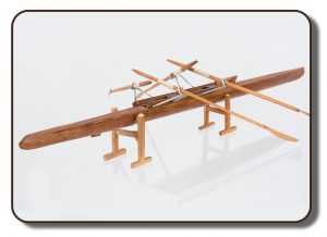 Image of a model of an early two-person rowing scull. This model is made of wood and measures approximately 10 inches long, there are four wooden oars attached by metal outriggers.
