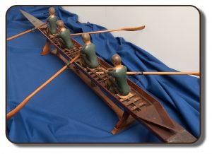 Image d'une réplique en bois du célèbre aviron J. A. Harding qui aurait été utilisé par l'équipage de Paris à la Régate internationale d'aviron, à Paris, en France. Ce modèle mesure environ 3 pieds de long et comprend quatre figurines représentant les quatre membres de l'équipage.