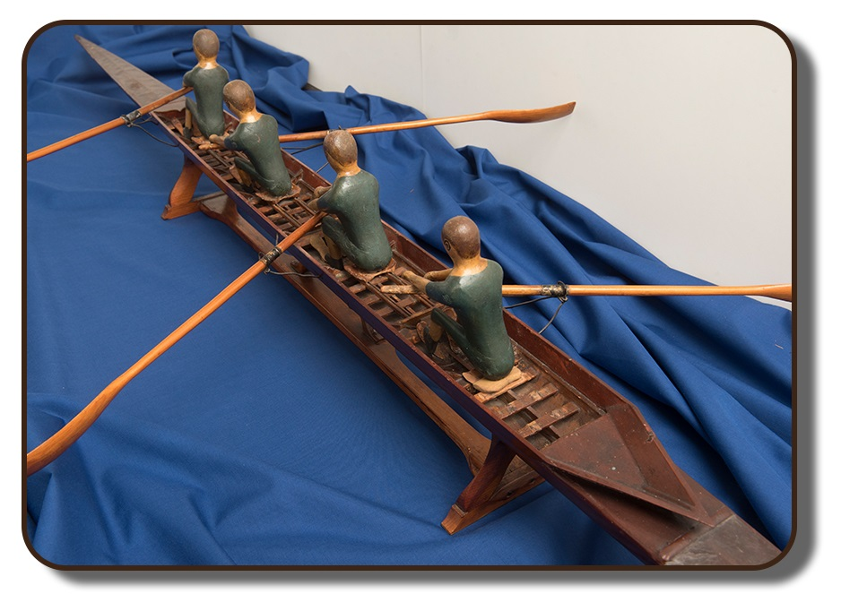 Image of a wooden replica of the famed J. A. Harding rowing scull that the Paris Crew would have competed with at the International Rowing Regatta in Paris, France. This model is approximately three feet in length, with four wooden figures representing the four team members.