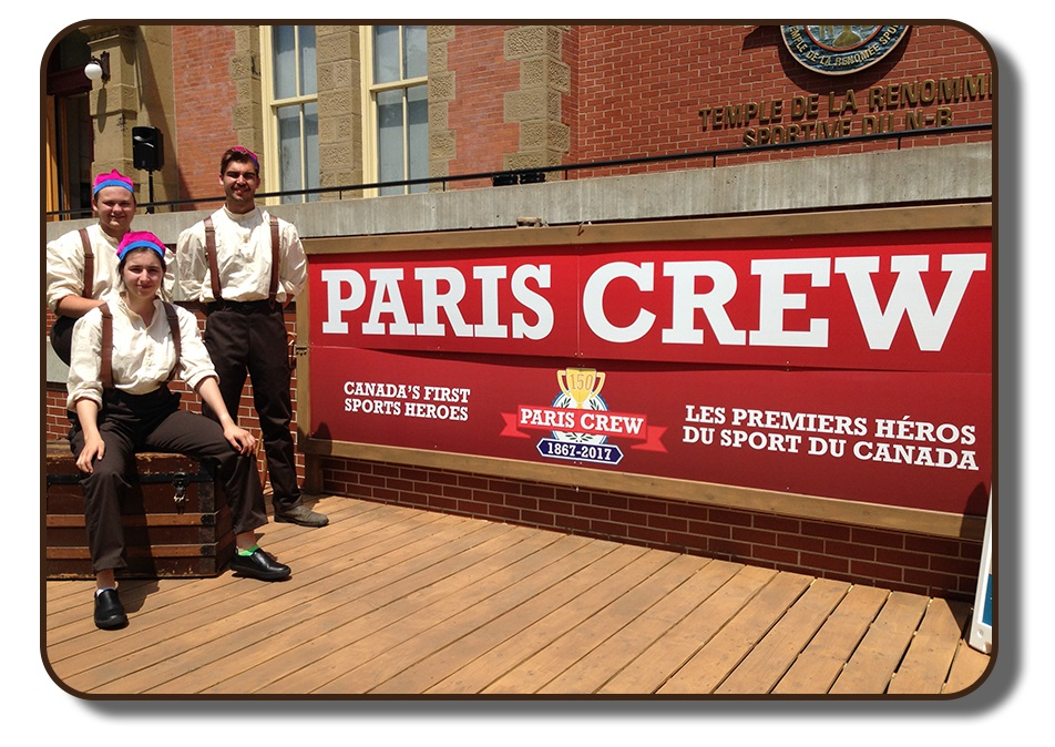 Image of an outdoor stage area in front of the New Brunswick Sports Hall of Fame. The stage is meant to resemble a wooden dock from that time period. Three performers are dressed in period clothing including brown pants, white linen shirts, brown leather suspenders and wearing the Paris Crew signature rowing caps. The backdrop of the stage area reads