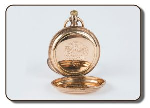 Image of a gold-coloured pocket watch with front and back hinged covers opened up to show the engaged markings on the back. The engraving shows that this particular pocket watch was presented to Samuel Hutton, member of the Paris Crew for rowing in 1867. The other hinged cover was used to protect the face of the watch, which is not visible from the angle shown.