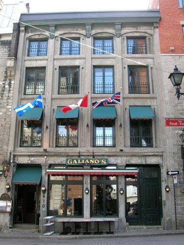 Colour photograph showing the façade of a four-storey building, with green shutters adorning some windows. The flags of Quebec, Canada and the United Kingdom, hung from the second floor, flutter in the breeze.