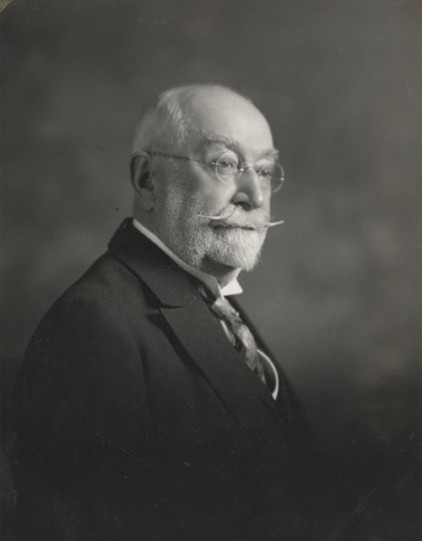 Black & white photograph of an older man with a short white beard and a long upturned moustache. He wears round eyeglasses, a white shirt with a tie, and a black jacket.