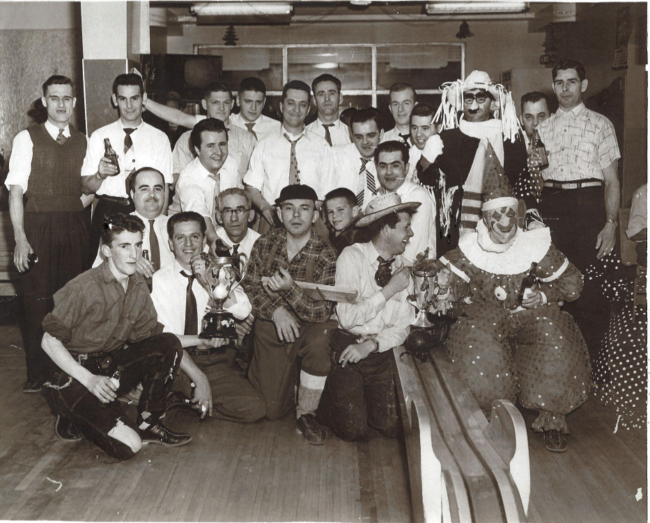 Black & white photograph of a group of men, some in costume, next to a bowling alley.