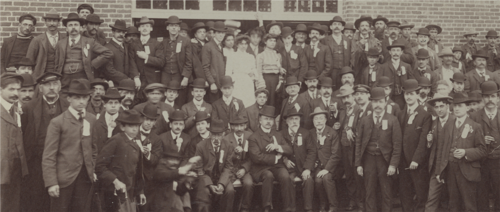 Sepia-tone photograph showing men and some women outside, in front of a paper mill.