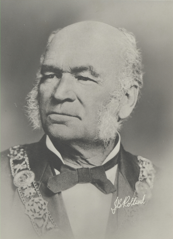 Portrait in black & white of an elderly man with white sideburns. He wears a white shirt with a black bow tie, and a dark jacket with ornamentation (a chain of office).