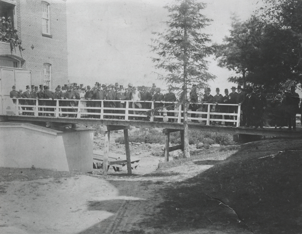Black & white photograph depicting several men and women standing on a bridge. Part of the Saint-Jérôme paper mill is seen at left, along with several trees at right.