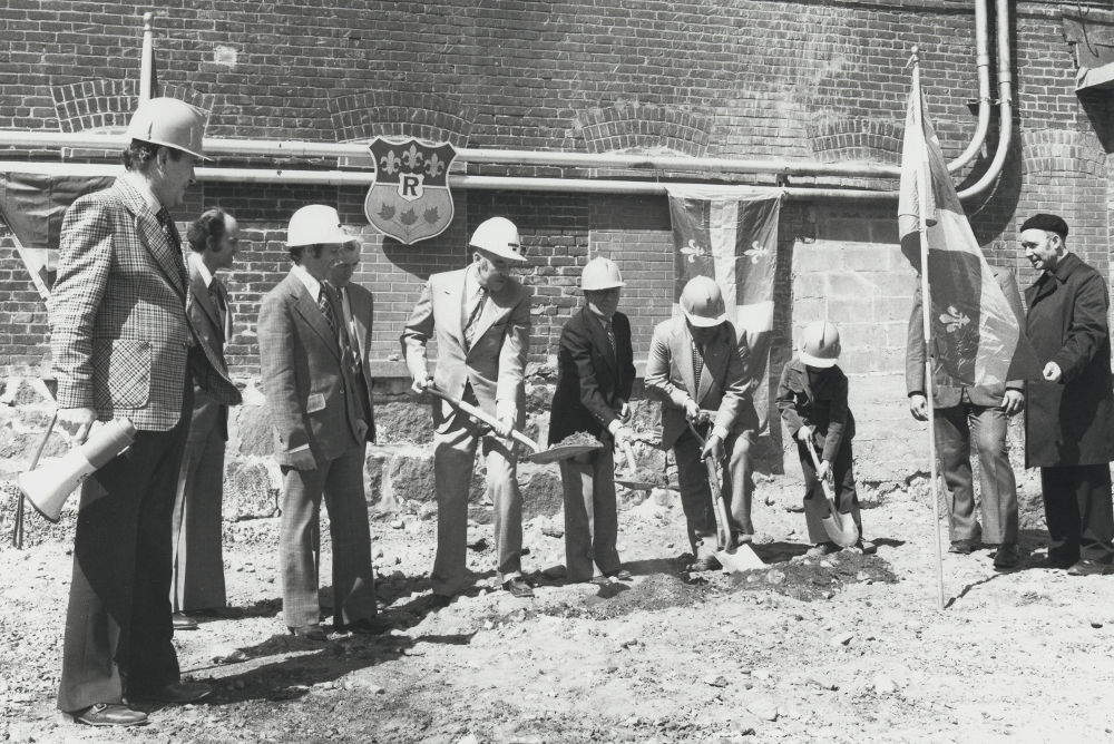 Black & white photograph depicting several men standing together, wearing suits and hardhats and holding shovels.
