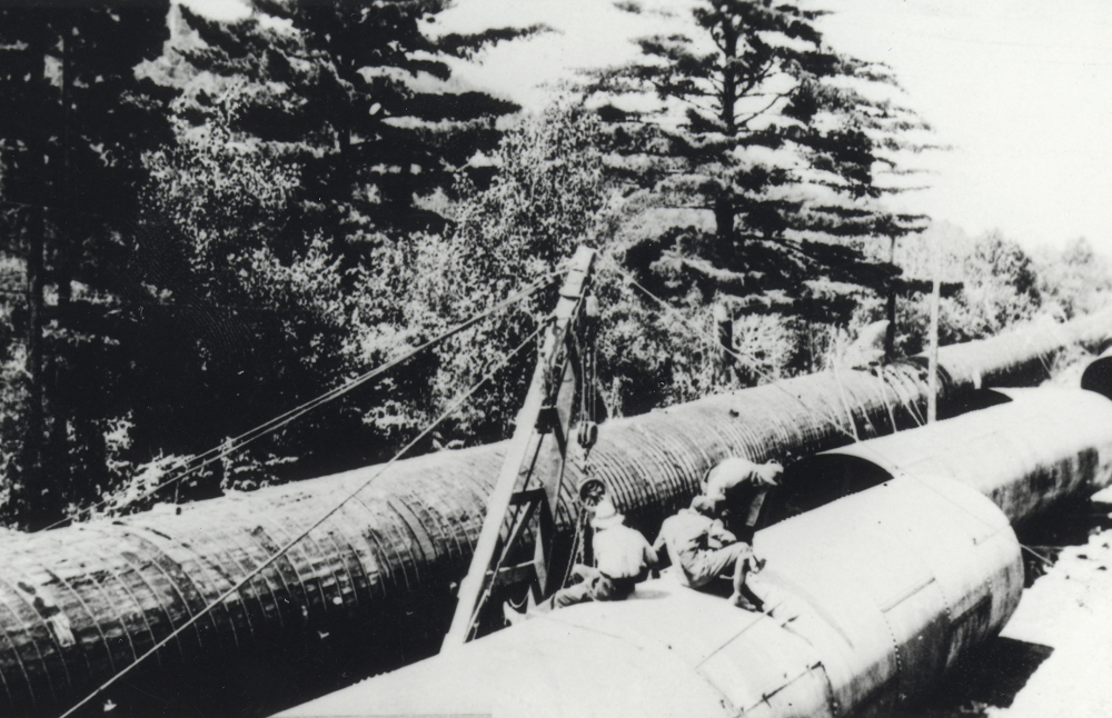 Black & white photograph showing workers next to large water pipes in a woodland.
