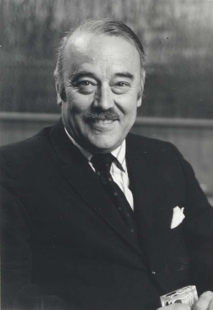 Black & white portrait of a smiling man in his forties or fifties, with a small moustache; he wears a dark suit and tie.
