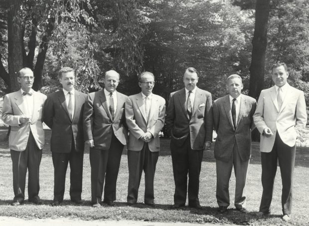 Black & white photograph of seven men standing together, outdoors.