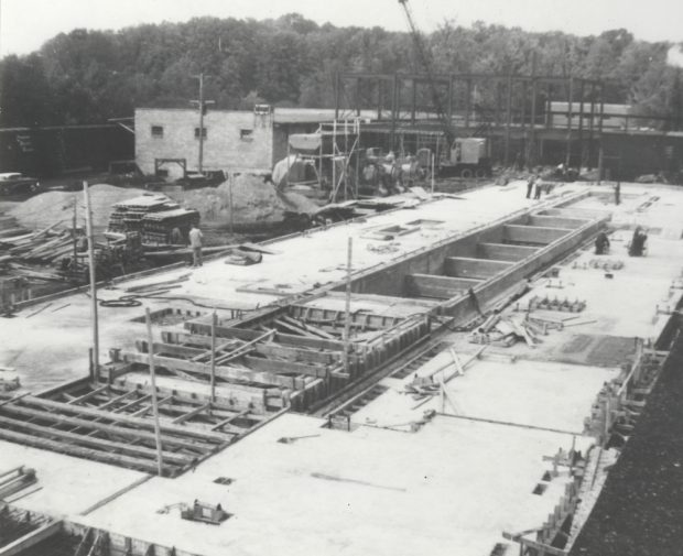 Black & white photograph of a building under construction, showing workers and machinery.