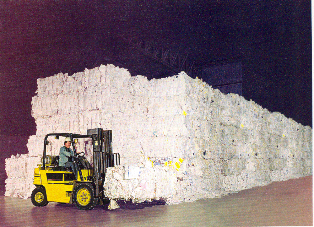 Colour photograph of a forklift in front of several piles of bales of scrap paper.