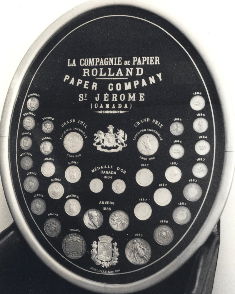 Black & white photograph of a large oval frame showcasing several medals.
