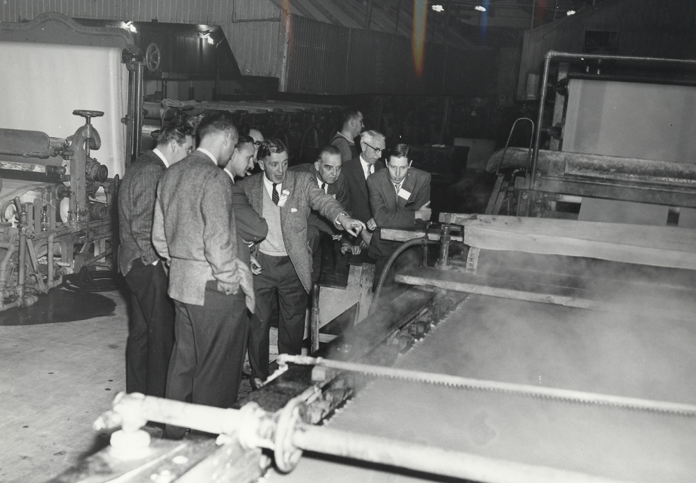 Black & white photograph depicting a group of men beside a paper machine. In the background, another machine is seen, at left, along with the interior of the plant.