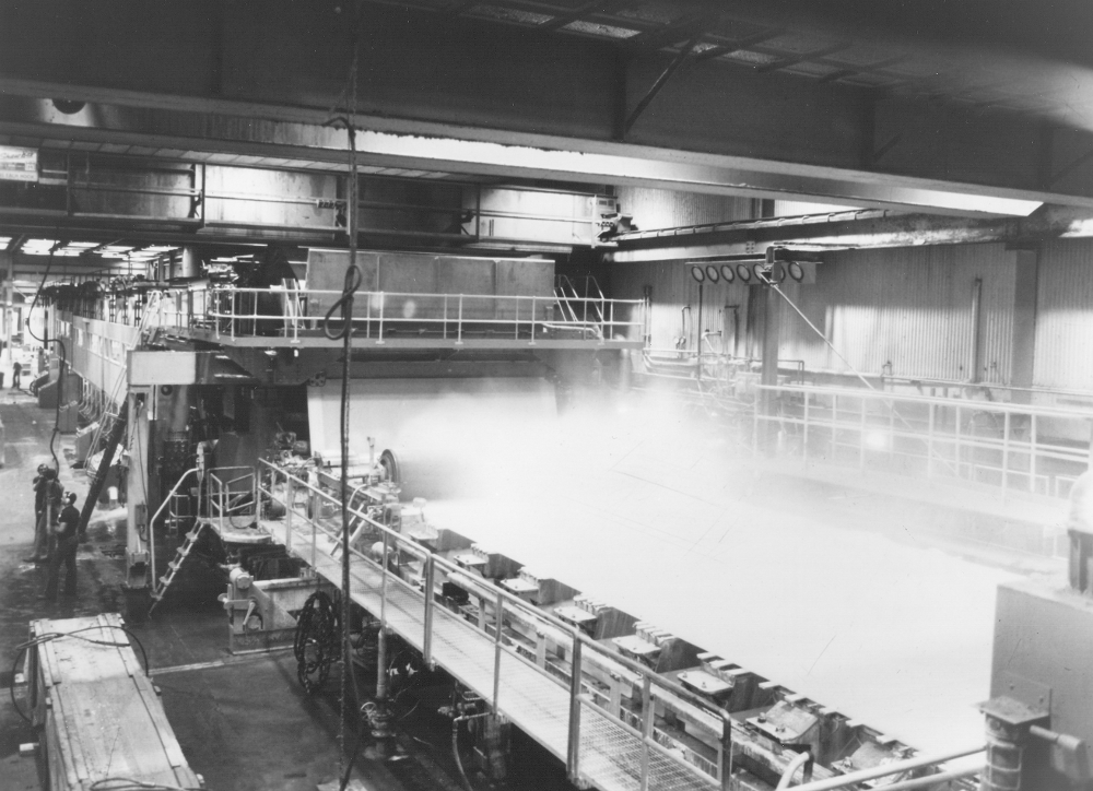 Black & white photograph of a working paper machine. Vapour escapes from one of the trays, visible in the foreground. On the left are workers close to the machine.