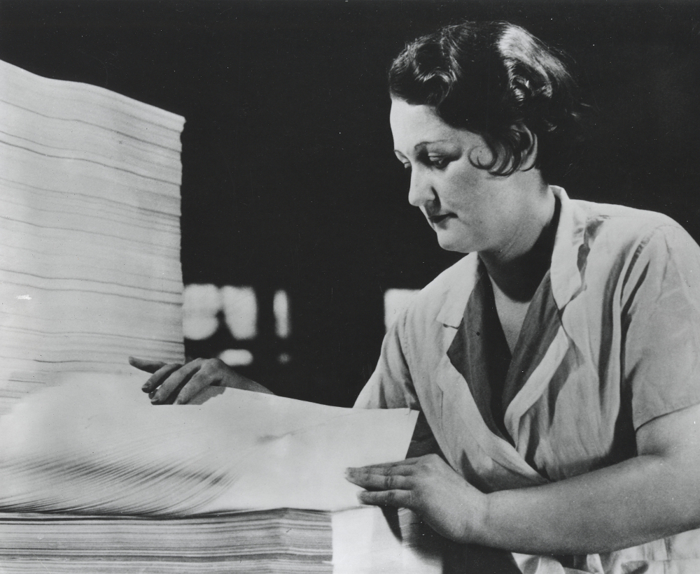 Black & white photograph depicting a woman counting a stack of sheets.