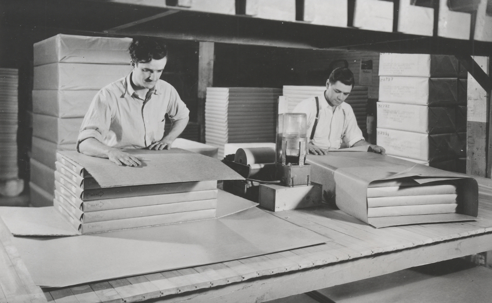 Black & white photograph depicting two men wrapping packets of paper. Behind them, already wrapped packets are seen.