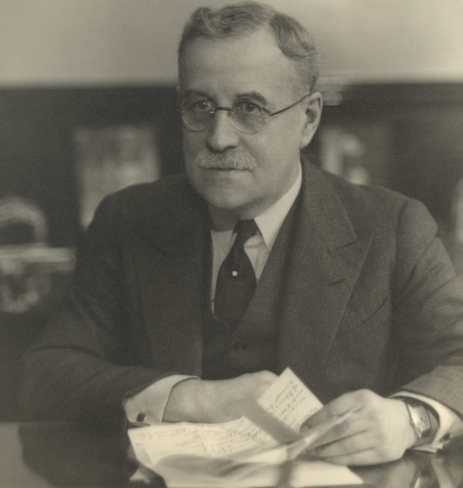 Black & white portrait of a man wearing glasses and a suit, seated at a desk and holding a sheet of paper.