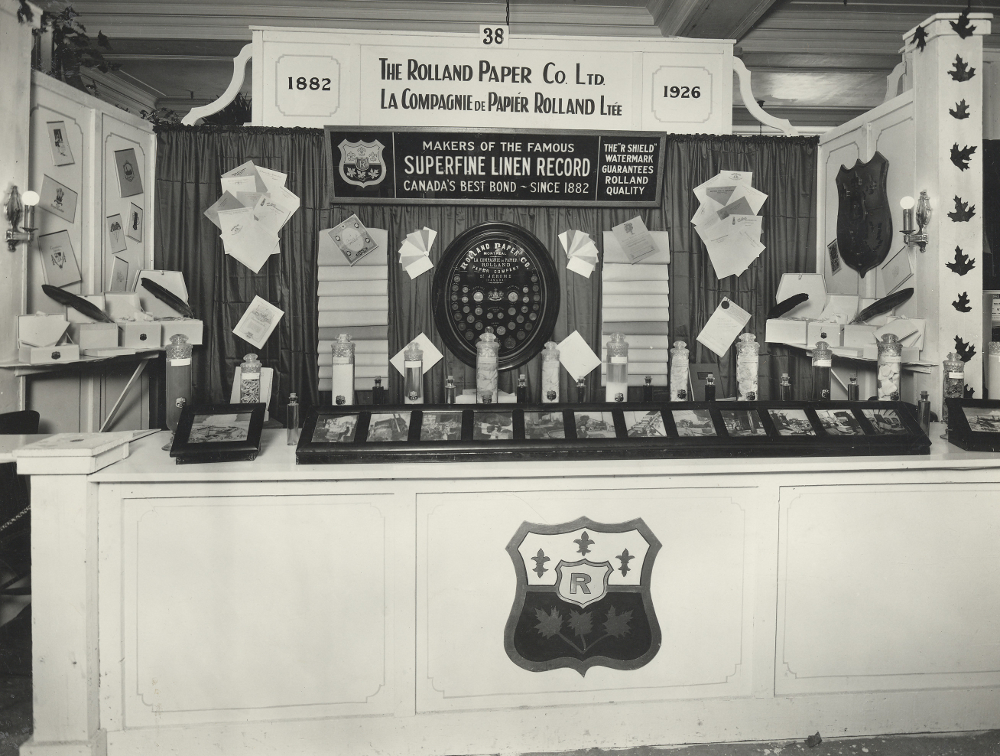 Black & white photograph of a stand displaying numerous photographs, paper samples and glass containers. Posters advertise the Rolland Company name.