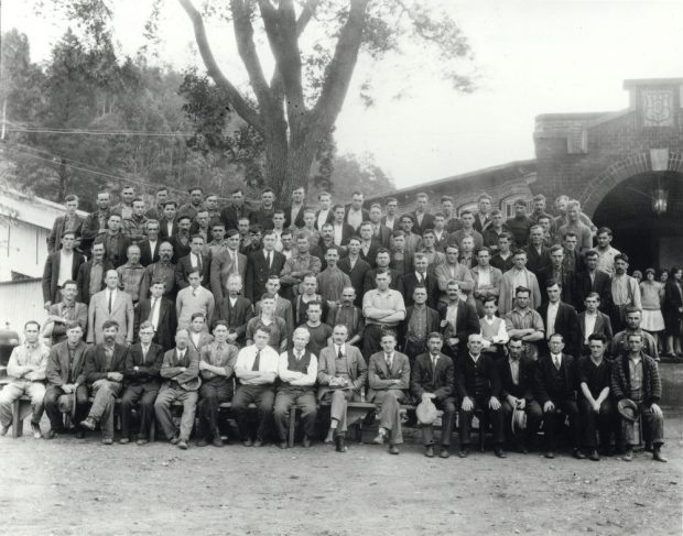 Black & white photograph large group of men standing in rows in front of a factory.
