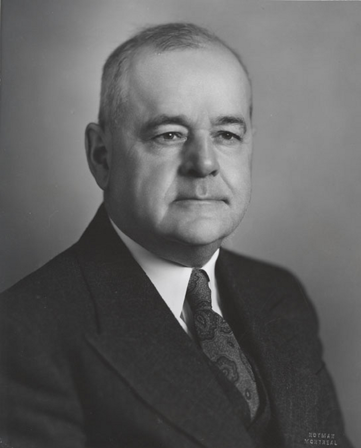Black & white photograph of a man wearing a suit and tie.
